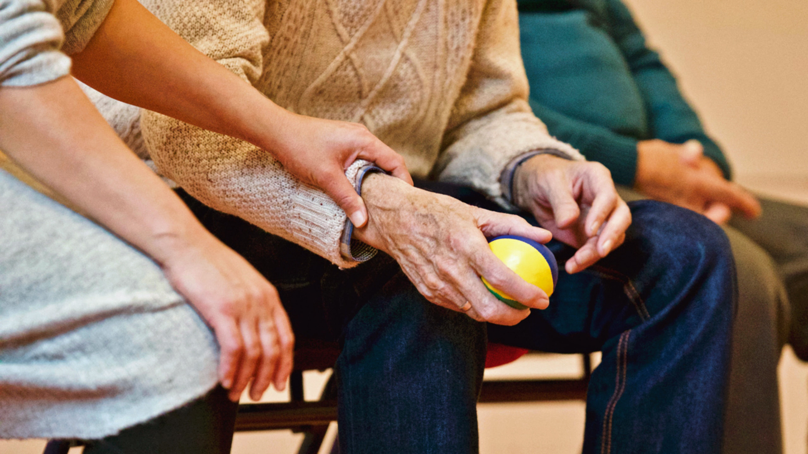Elderly man holding a ball.